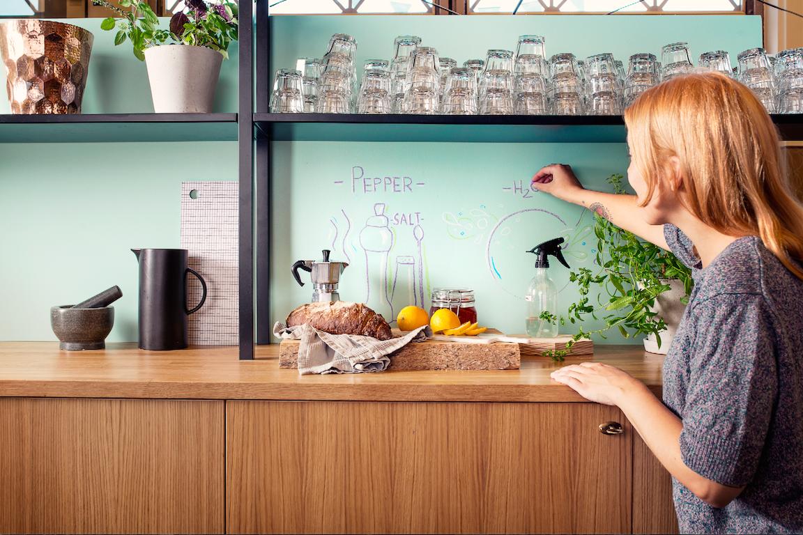 Kobieta ozdabiająca ścianę w kuchni poprzez rysowanie po niej kredą.