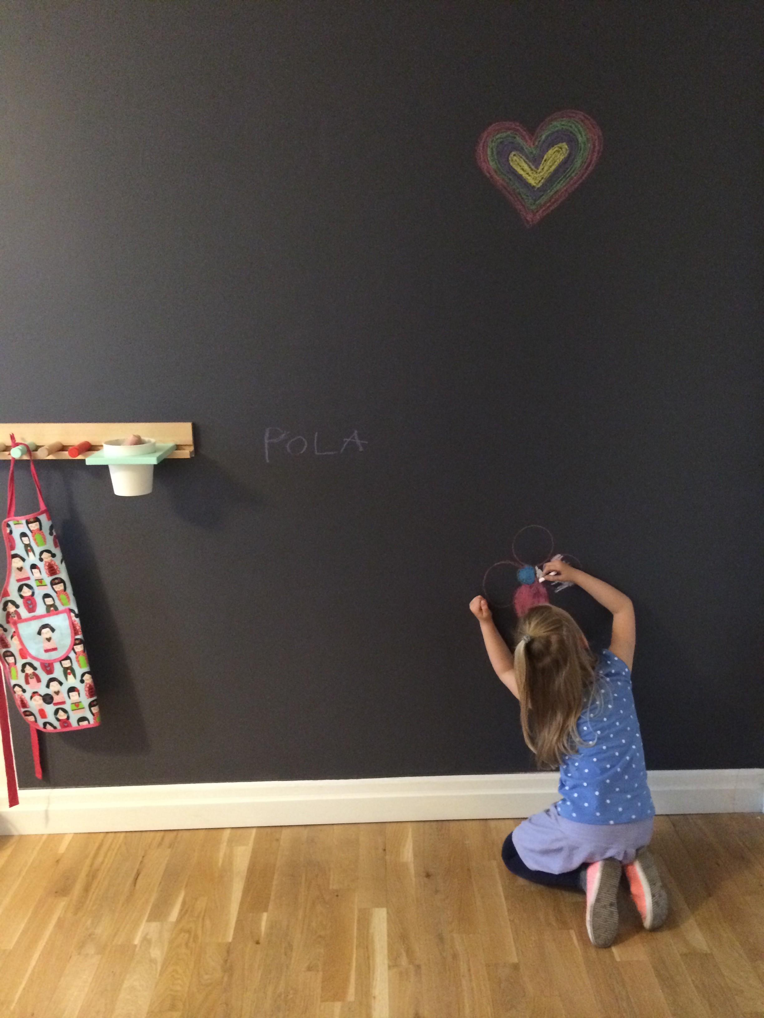 Dziewczynka rysująca kredą po ścianie pomalowanej farbą tablicową.