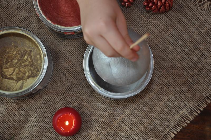 dziecko zanurza styropianową bombkę w puszce srebrnej farby Tikkurila Taika Pearl Paint